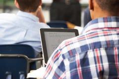 Männlicher Schüler, der Digital-Tablette im Klassenzimmer verwendet stockbilder