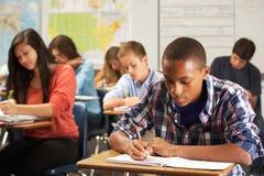 Männlicher Schüler, der am Schreibtisch im Klassenzimmer studiert Stockfotos