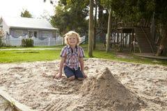 Männlicher Schüler an Montessori-Schule, die im Sand Pit At Breaktime spielt Stockfotografie