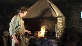 Männlicher Schmied, der durch das Brennen des Feuers arbeitet Schmied, der ein Hufeisen auf einem Ambosse schmiedet Volles HD stock video