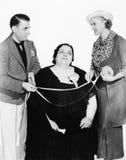 Männlicher Schneider und sein Assistent, die eine überladene Frau mit einem messenden Band misst (alle dargestellten Personen sin Stockfoto