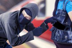 Männlicher Schuft, der Smartphone von seinem Opfer stiehlt lizenzfreie stockfotos