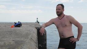 Männlicher Schwimmer mit einem Bart steht auf einem konkreten Pier, nachdem er im Meer im Hintergrund einen Leuchtturm geschwomme stock video footage