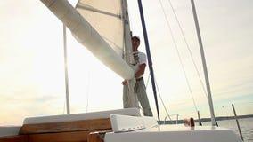 Männlicher Seemann, der herauf Segel auf Yacht, Sonnenuntergang, goldene Stunde sich setzt stock video