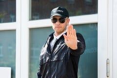Männlicher Sicherheitsbeamte Making Stopp Sign mit der Hand Stockfotografie