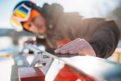 Männlicher Skifahrer überprüft Skis, bevor er, Wintersport Ski fährt Lizenzfreie Stockfotos