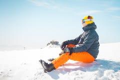 Männlicher Skifahrer, der auf dem Entspannungsc$schauen des Schnees im Abstand sitzt Stockbilder