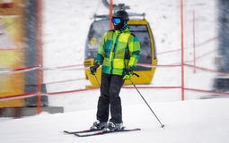 Männlicher Skifahrer, der hinunter die Steigung am Schneesturm reitet Lizenzfreies Stockfoto