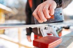 Männlicher Skifahrer dient Skis, bevor er, Wintersport Ski fährt Stockfoto