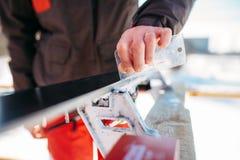 Männlicher Skifahrer dient Skis, bevor er, Wintersport Ski fährt Stockfotos