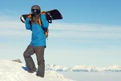 Männlicher Snowboarder, der einen Blick auf Landschaft beim Klettern zur Spitze des Berges wirft Lizenzfreie Stockfotos