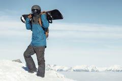 Männlicher Snowboarder, der einen Blick auf Landschaft beim Klettern zur Spitze des Berges wirft Gefiltertes Bild: Kreuz verarbei Lizenzfreie Stockbilder