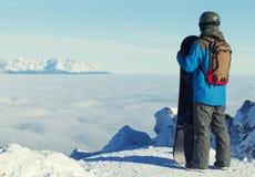 Männlicher Snowboarder, der einen Blick auf Landschaft an der Spitze des Berges wirft Lizenzfreie Stockbilder