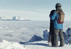 Männlicher Snowboarder, der einen Blick auf Landschaft an der Spitze des Berges wirft Gefiltertes Bild: Kreuz verarbeiteter Weinl Lizenzfreie Stockfotografie