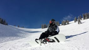 Männlicher Snowboarder, der hinunter den Berg schiebt Stockbilder