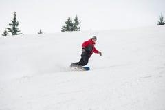 Männlicher Snowboarder, der unten vom Berg am Wintertag reitet Lizenzfreie Stockfotografie