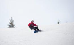 Männlicher Snowboarder, der unten vom Berg am Wintertag reitet Stockfotografie