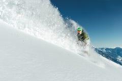 Männlicher Snowboarder kurvte und die Bremsen, die losen tiefen Schnee auf f sprühen Lizenzfreies Stockfoto