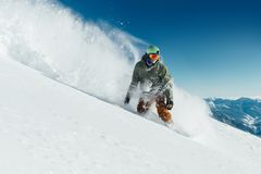 Männlicher Snowboarder kurvte und die Bremsen, die an losen tiefen Schnee sprühen Stockbild