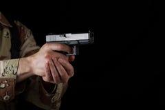 Männlicher Soldat, der seine Waffe in der Dunkelheit zeigt Stockfoto