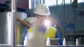 Männlicher Spezialist betreibt eine Tablette nahe dem Förderer, der Plastik verlagert stock footage