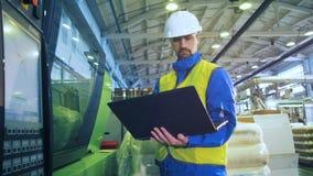 Männlicher Spezialist betreibt einen Laptop bei der Stellung nahe Bedienfeld stock footage