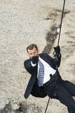 Männlicher Spion, der Pistole beim Rappelling zielt Stockbild