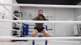 Männlicher springender Kämpfer, während Training auf Boxring aufwärmen Sie Boxermann, der Sprungsübung im Kampfverein tut Sporttr stock footage