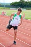 Männlicher Sprinter, der vor einem Rennen ausdehnt Lizenzfreie Stockfotografie