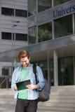 Männlicher Student auf dem Campus, der auf Notizblock schreibt Stockbilder