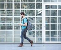 Männlicher Student, der auf dem Campus mit Tasche und Handy geht Lizenzfreies Stockbild