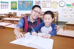 Männlicher Student, der in der Klasse mit Lehrer lernt stockfotos
