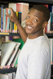 Männlicher Student, der für ein Bibliotheksbuch erreicht Stockfotos