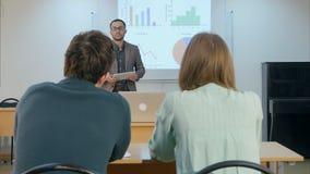 Männlicher Student, der Hand anhebt und Lehrer eine Frage sitzt auf Tabelle stellt lizenzfreies stockbild