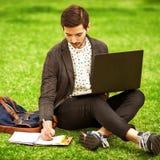 Männlicher Student der jungen Mode, der auf Gras sitzt Stockfotos