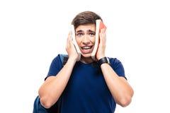 Männlicher Student, der sein Gesicht mit Büchern bedeckt Lizenzfreie Stockfotografie