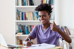 Männlicher Student des Afroamerikaners, der für Prüfung sich vorbereitet lizenzfreie stockbilder