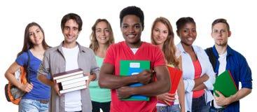 Männlicher Student des glücklichen Afroamerikaners mit Gruppe Studenten stockfotografie