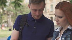 Männlicher Student explaines etwas im Notizbuch zu seinem Mitschüler auf dem Campus stockfotos