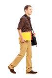 Männlicher Student mit der Umhängetasche, die Bücher und das Gehen anhält Lizenzfreie Stockfotos