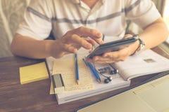 Männlicher Student unter Verwendung des Mobiltelefons beim Studieren mit Arbeitsbuch auf Tabelle stockbilder