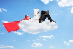 Männlicher Superheld, der auf Wolke liegt und eine Zeitung liest Lizenzfreie Stockbilder