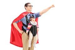 Männlicher Superheld mit der angehobenen Faust, die ein Baby trägt Lizenzfreie Stockbilder