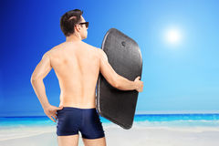 Männlicher Surfer, der ein Surfbrett hält und in Richtung des Meeres blickt Stockbilder