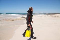 Männlicher Taucher mit Taucheranzug-Schnorchelmaskenflossen auf dem Strand Lizenzfreies Stockfoto