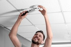 Männlicher Techniker, der zuhause Rauchmeldersystem installiert stockfotografie