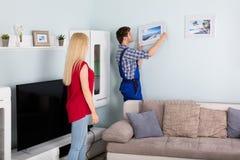 Männlicher Tischler Hanging Picture Frame auf Wand Lizenzfreie Stockfotografie