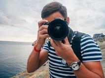 Männlicher Tourist des Fotografen mit einer Digitalkamera und einer großen Linse Stockbilder