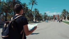 Männlicher Tourist liest die Karte der Stadt an gehend nahe Arc de Triomphe in Barcelona stock video footage