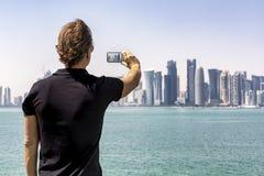 Männlicher Tourist macht ein Foto der Skyline von Doha, Katar lizenzfreie stockfotografie